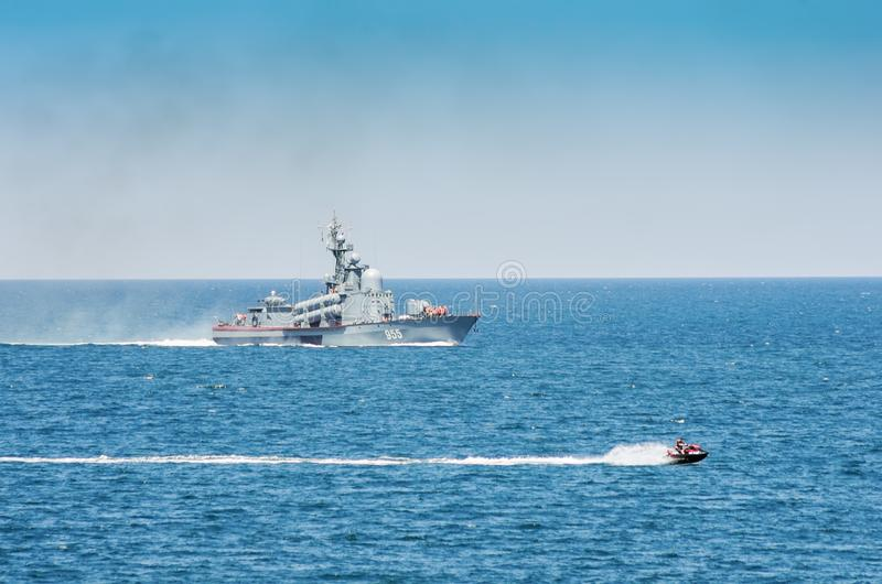 A warship and a hydrocycle in the sea. Russia, the Black Sea. 06/11/2018: Jet ski and small missile ship of the Russian navy on the high seas royalty free stock photography