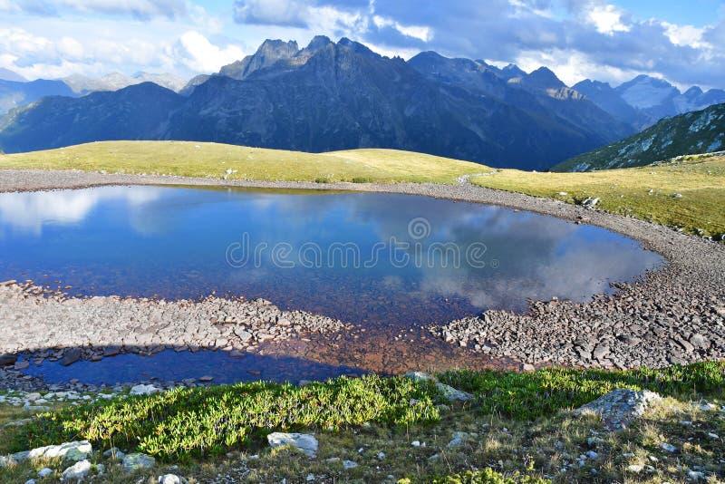 Russia, Caucasus, Arkhyz. Lower Kara-su lake and Kara-Jash mountain 3.201 m in cloudy weather royalty free stock image