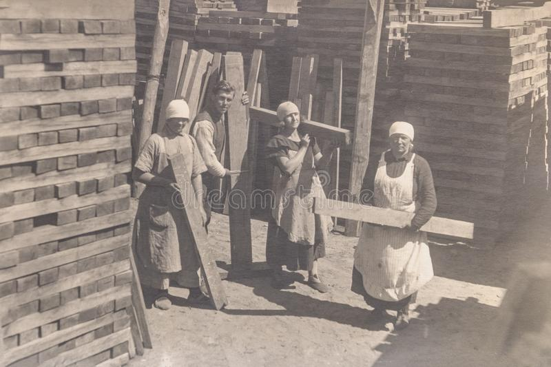 RUSSIA - CIRCA 1920s: Vintage photo of thee young women and man working in manufacture stock image