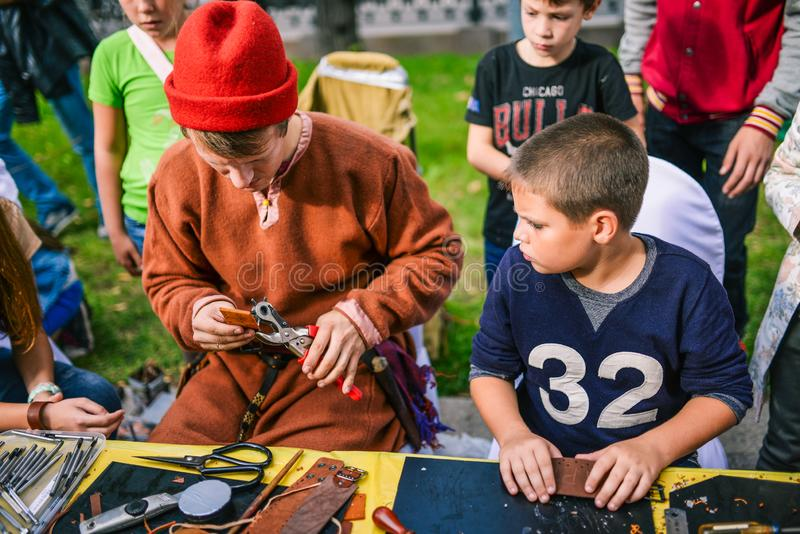 Russia, city Moscow - September 6, 2014: The child observes the master, who makes leather goods. Master class for the royalty free stock image
