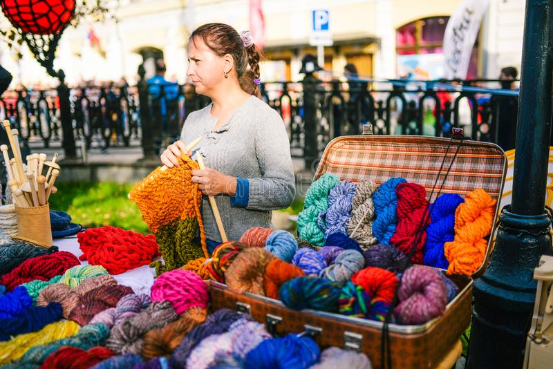 Russia, city Moscow - September 6, 2014: Woman knits on the street. Women`s hands knit a colorful product made of wool royalty free stock photography