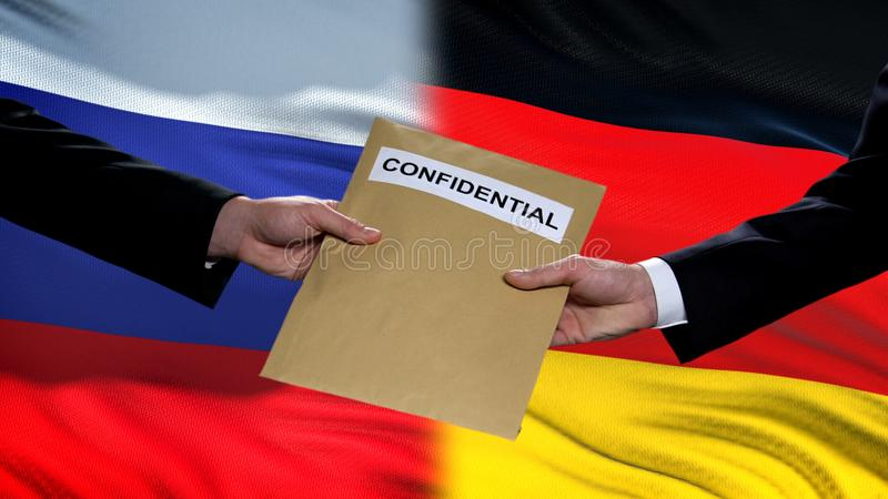 Russia and Germany officials exchanging confidential envelope, flags background. Stock photo royalty free stock photography