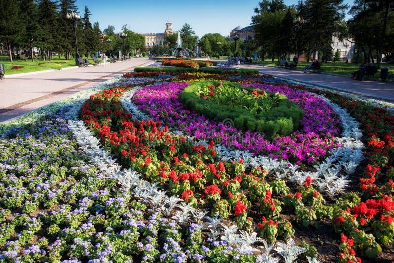 Russia, Irkutsk - July 7, 2019: Flower bed, fountain and historical building in Tikhvinsky or Kirov Square in sunny. Russia, Irkutsk - July 7, 2019: Flower bed stock photos