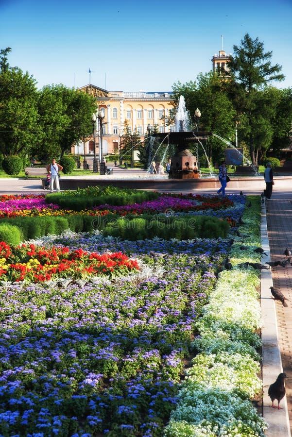 Russia, Irkutsk - July 7, 2019: Flower bed, fountain and historical building in Tikhvinsky or Kirov Square in sunny. Russia, Irkutsk - July 7, 2019: Flower bed stock photo