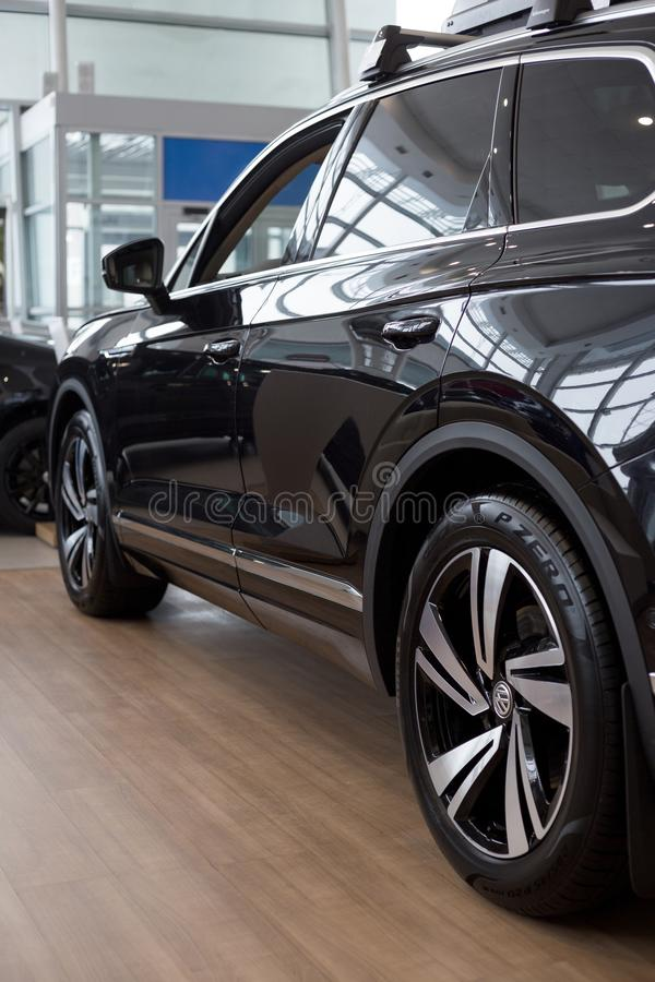 Russia, Izhevsk - February 15, 2019: Showroom Volkswagen. New Touareg in dealer showroom. End view. Famous world brand stock image