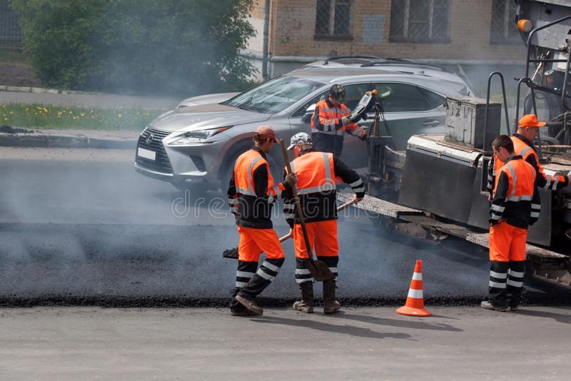 Russia, Izhevsk - May 30, 2018: Road building. Repair and replacement of old asphalt pavement. Men at work. Asphalt layover stock photo