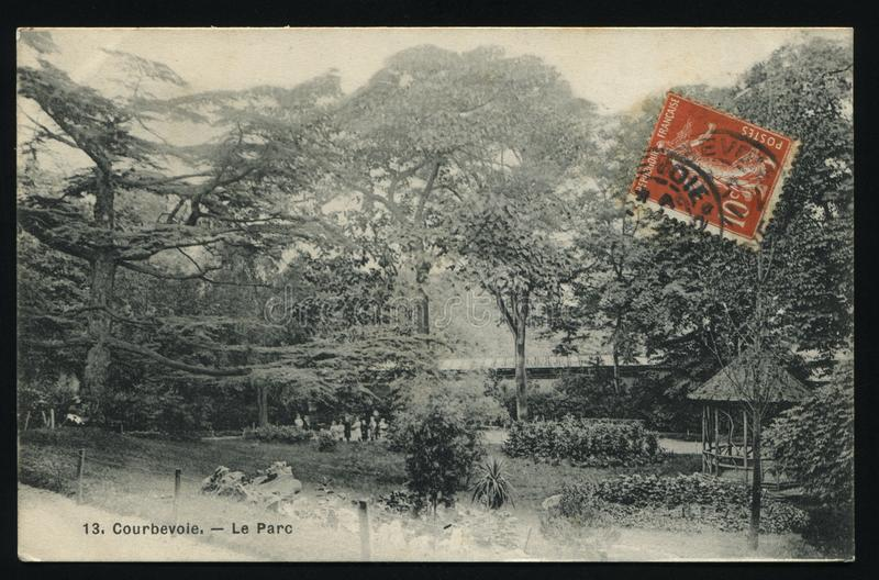 Courbevoie in Paris postcard. RUSSIA KALININGRAD, 29 MAY 2017: postcard printed by France shows the park in the commune Courbevoie in Paris, circa 1910 royalty free stock images
