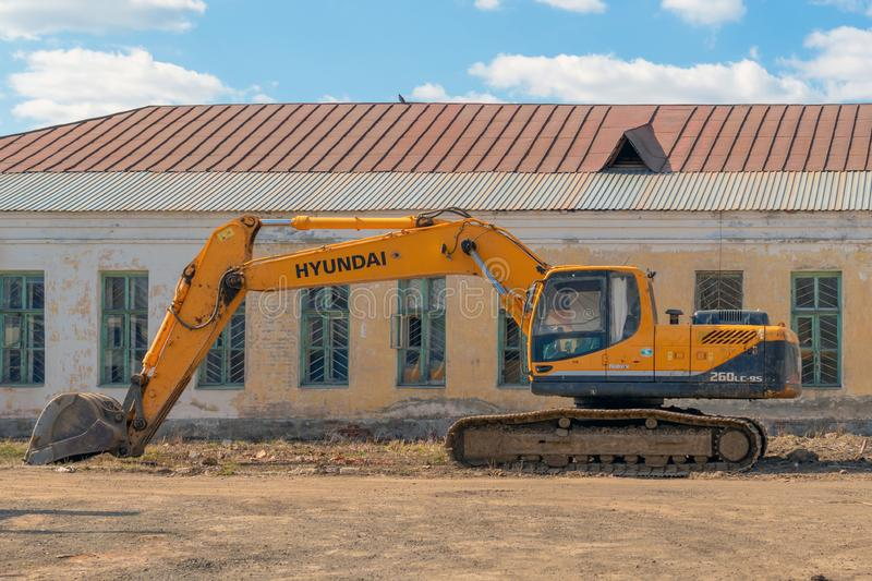 Russia, Kazan - April 20, 2019: Yellow excavator on the background of an abandoned building. stock image