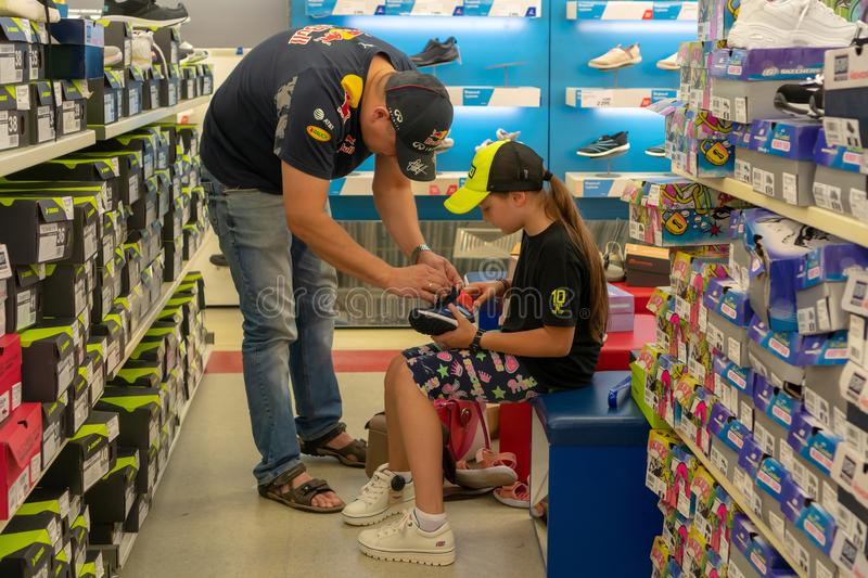 Russia, Kazan - August 10, 2019: Dad and daughter choose sports shoes in the store. Preparation for school. Back to school royalty free stock photo