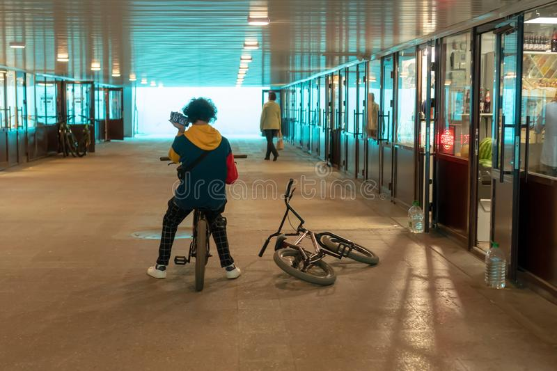Russia, Kazan - August 8, 2019: Stylish teenager boy on a bicycle with a phone in his hands listens to a voice message in a subway. Passage royalty free stock image