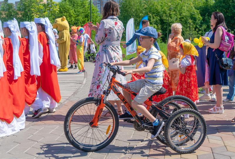 Russia, Kazan - May 31, 2019: Disabled boy with glasses on a four-wheeled bicycle on a bright sunny day. Charity bike ride. stock photo