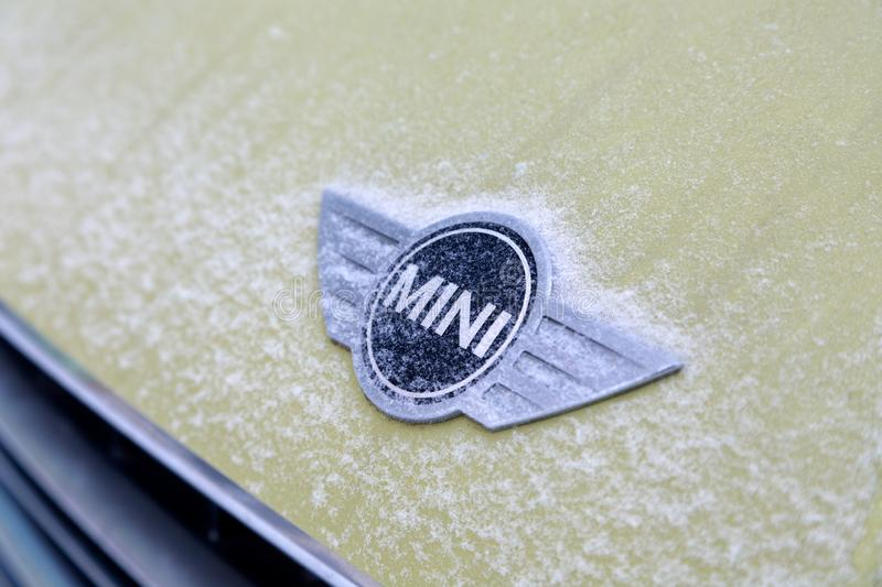 Russia Kemerovo 2019-01-07 Close view of Mini Cooper car logo badge on yellow Mini Cooper car covered snow royalty free stock image