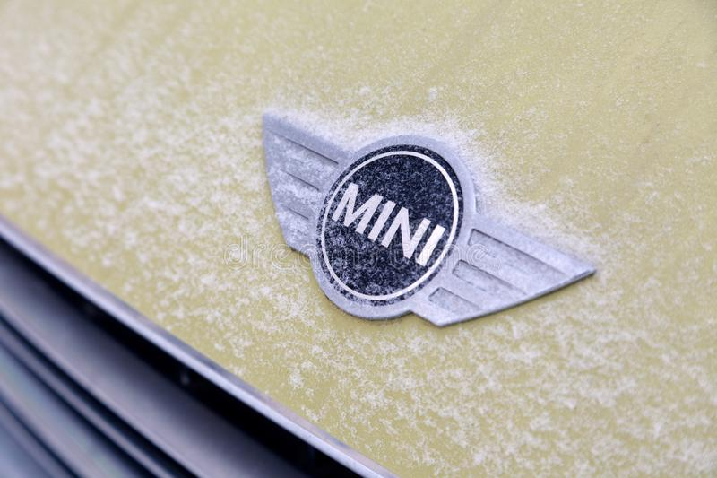 Russia Kemerovo 2019-01-07 Close view of Mini Cooper car logo badge on yellow Mini Cooper car covered snow royalty free stock photos