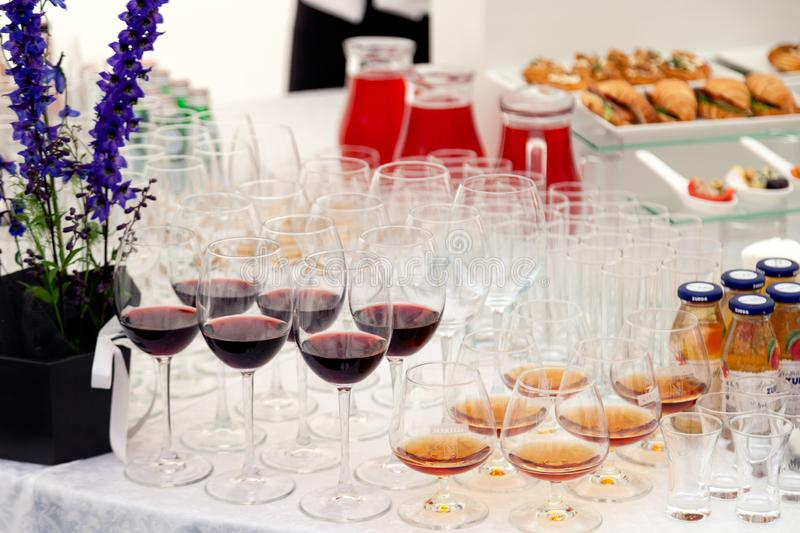 Russia Kemerovo 2019-07-27 Closeup catering modern setting, glasses with red wine, cognac, brandy, small bottles with juice, jugs stock photo
