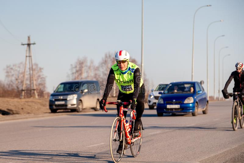 Russia Kemerovo 2019-04-11 Cycling competition, cyclist athletes in helmet and uniform tinkoff team riding race at high speed on stock image