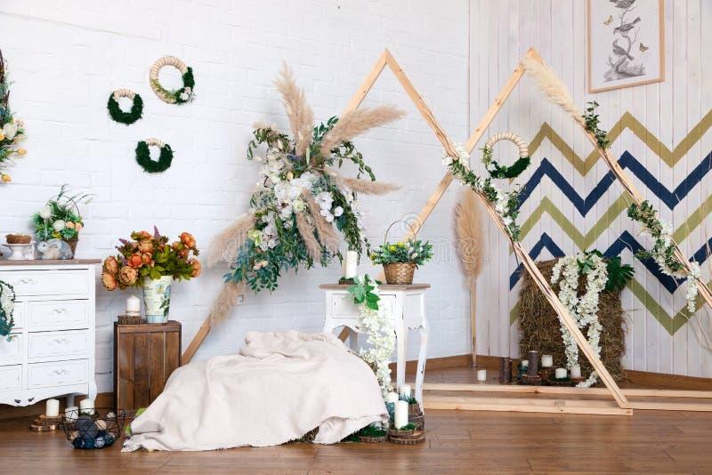 Russia Kemerovo 2019-04-15 Spring design of interior photo studio: wooden triangle frames, wicker wreaths, basket, straw, bouquet. Pastel blanket, white chest royalty free stock photo