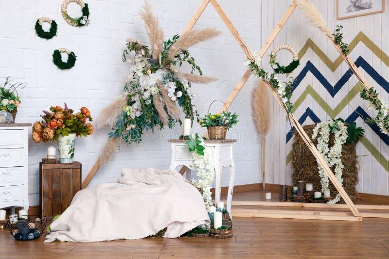 Russia Kemerovo 2019-04-15 Spring design of interior photo studio: wooden triangle frames, wicker wreaths, basket, straw, bouquet. Pastel blanket, white chest stock image