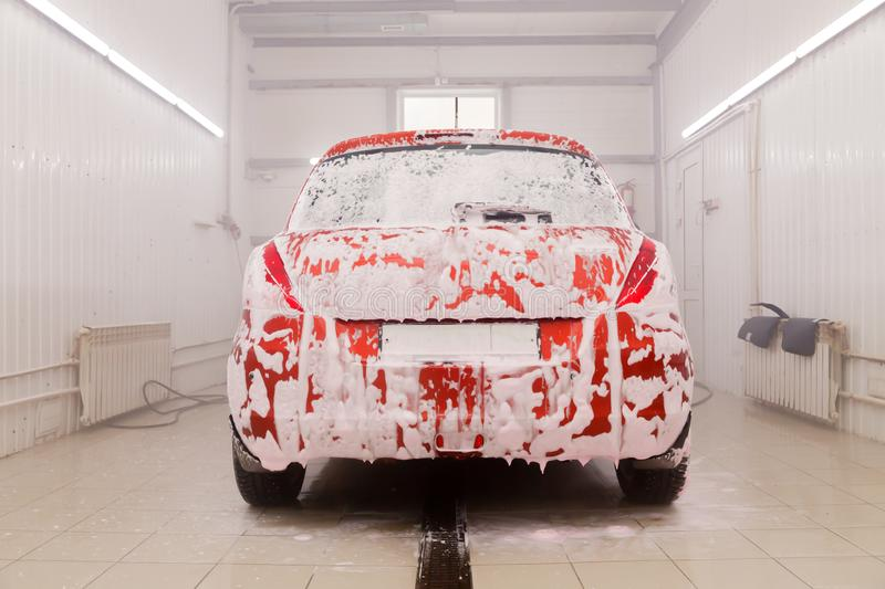 Russia Kemerovo 2019-01-05 Suzuki Swift bright red small car at car wash in white foam, professional chemical detergent for stock photo