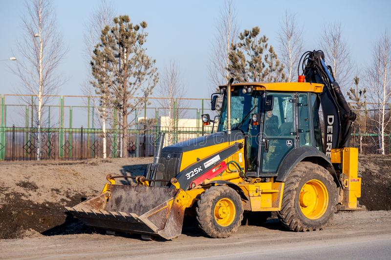 Russia Kemerovo 2019-04-11 Wheel tractor excavator loader with bucket. Concept construction works in industrial site, worksite stock image
