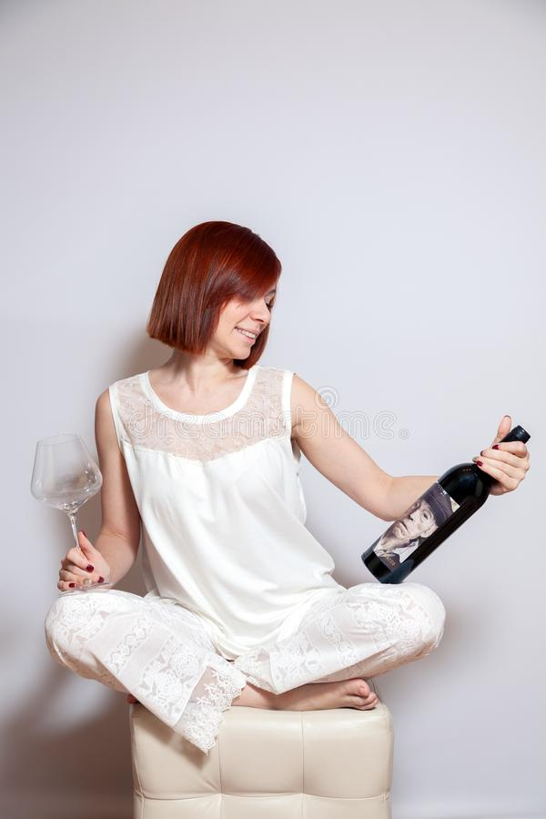 Russia Kemerovo 2018-12-23 Young beautiful girl holding a bottle of Spanish wine Matsu El Viejo and empty transparent crystal. Russia Kemerovo 2018-12-23 Young stock photo
