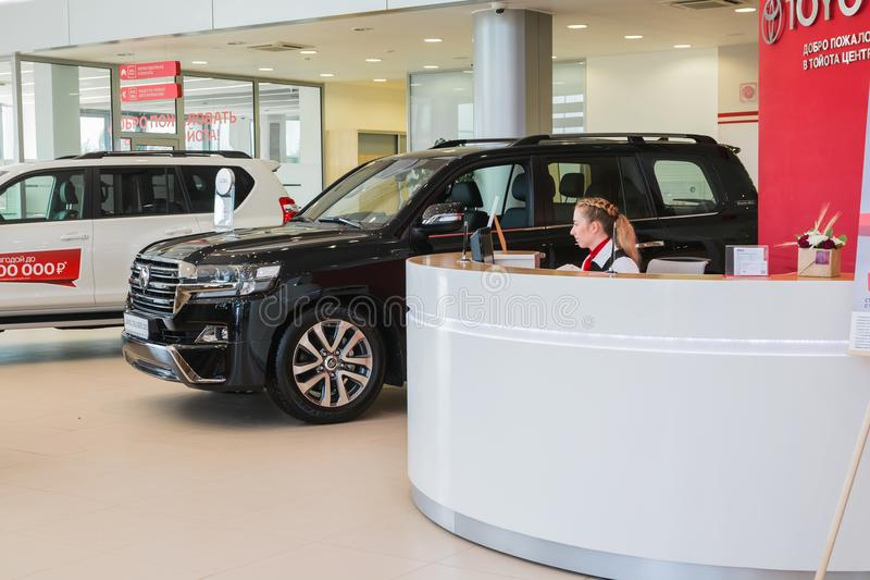 Manager and car in showroom of dealership Toyota in Kirov city in 2016. Russia, Kirov - August 21, 2017: Manager and car in showroom of dealership Toyota in stock photos