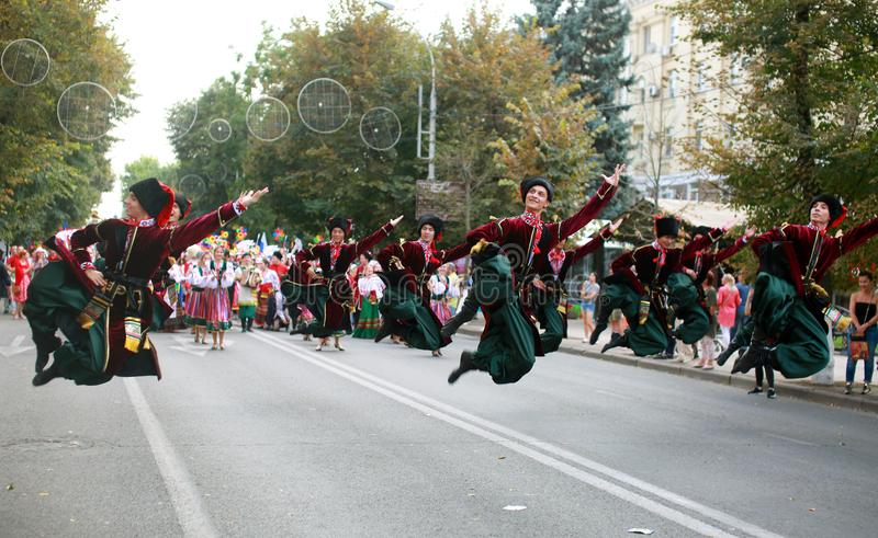 Procession of students of the Institute of culture, dancers in Cossack traditional dress, colored skirt, green trousers and maroon. Russia, Krasnodar 23.09.17 stock photography