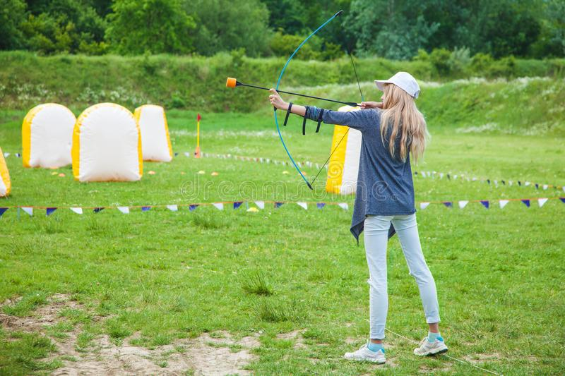 Russia Krasnodar Territory May 12,2018 Young blond girl shoots with an arrow stock photography