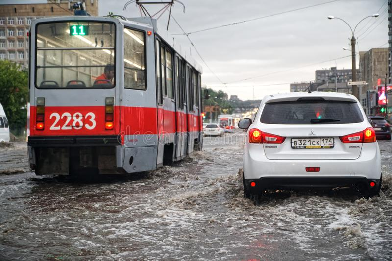Russia, Magnitogorsk, August 13, 2019. The consequences of summer rain in the city. Flooded city streets. Trams and cars in stock photo