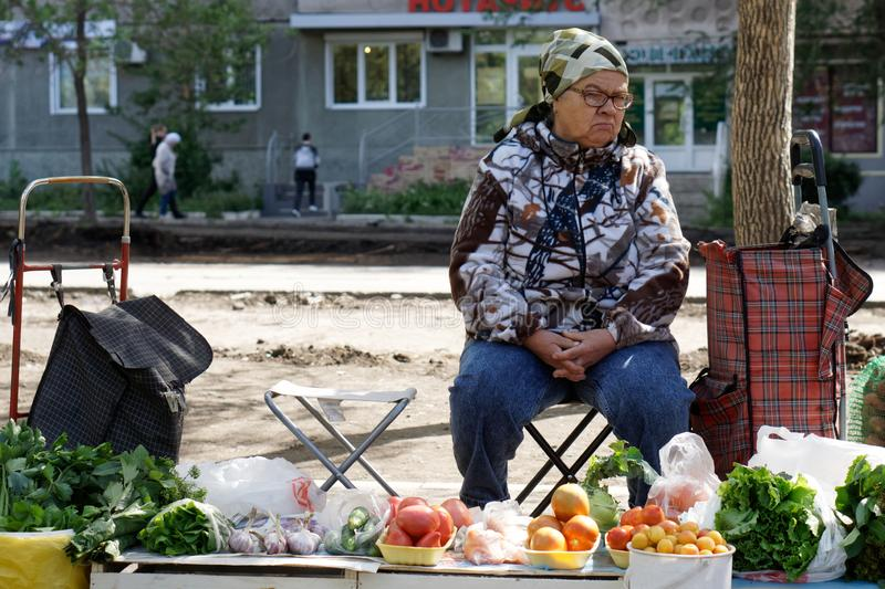 Russia, Magnitogorsk, August 6, 2019. Street trading in the city. An elderly woman sells vegetables grown in a private household royalty free stock photos