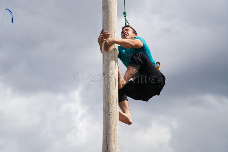 Russia, Magnitogorsk, - June, 15, 2019. A young man climbs on a wooden pole for gifts during Sabantuy - the national holiday of stock image