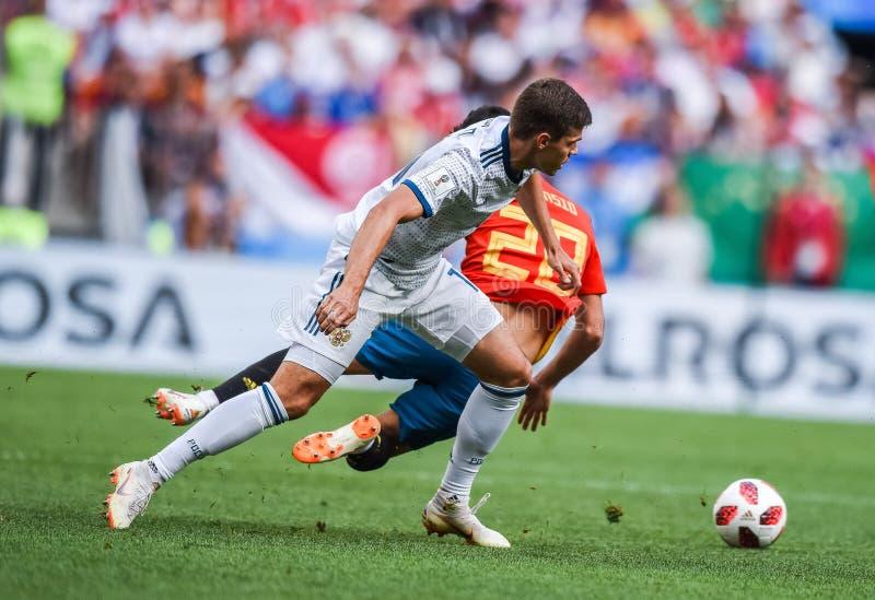 Russia midfielder Roman Zobnin against Spain national football team midfielder Marco Asensio. Moscow, Russia - July 1, 2018. Russia midfielder Roman Zobnin stock image