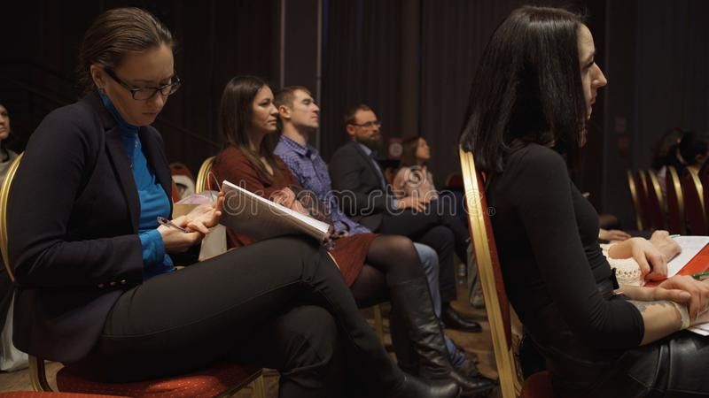 RUSSIA, MOSCOW - APRIL 13, 2019: Women`s audience listening to information trainings and lectures. Art. Women sitting in. Hall during speech about feminism, its stock photos