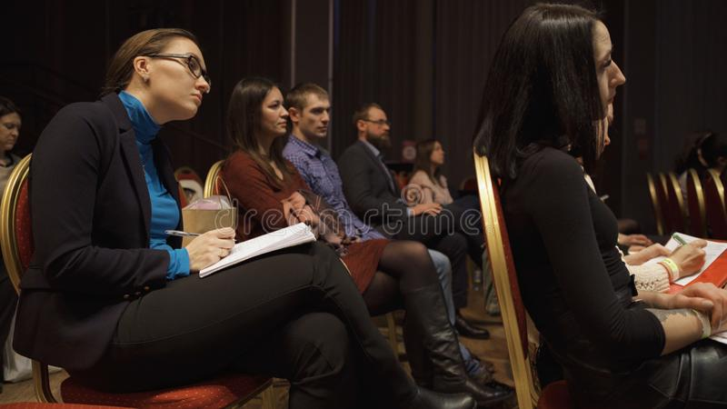 RUSSIA, MOSCOW - APRIL 13, 2019: Women`s audience listening to information trainings and lectures. Art. Women sitting in. Hall during speech about feminism, its stock photography