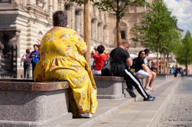 Russia Moscow 2019-06-17 Back view of fat woman in yellow dress sitting on bench, looking at St. Basil's Cathedral. People walk o. N Red Square. Concept tourism royalty free stock photos