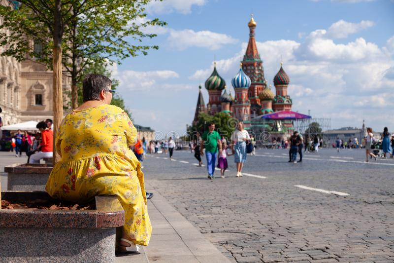 Russia Moscow 2019-06-17 Back view of fat woman in yellow dress sitting on bench, looking at St. Basil's Cathedral. People walk o. N Red Square. Concept tourism royalty free stock photography