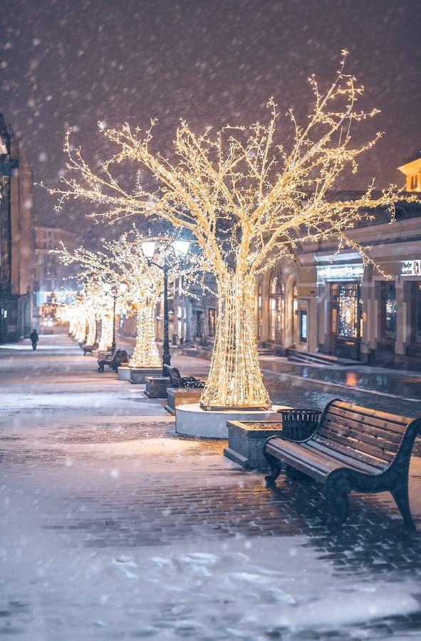 New Year`s scenery on Kuznetsky Most. Night illumination. Lanterns wine glasses and golden trees. Snowy night. stock photo