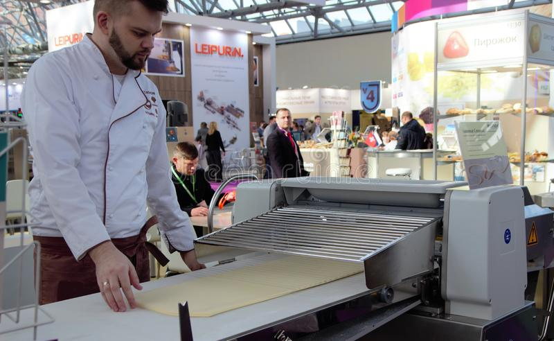 03.14.2019 Russia, Moscow. Exhibition Modern Bakery Moscow. the chef rolls the dough using a production machine. Selected focus. royalty free stock photography