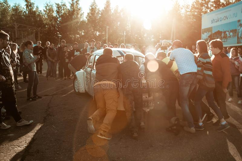 Russia, Moscow - July 06, 2019: A group of people trying to start the engine of an old Volkswagen beetle. They push him. Very stock photos