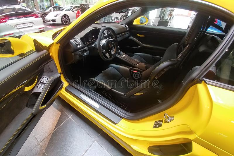 Russia, Moscow - May 04, 2019: Open driver door cockpit and Interior of Yellow Porsche Cayman GT4. Racing car in the dealer stock photography