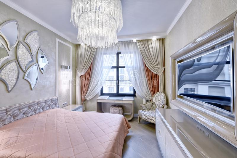 Modern interior of a bedroom in the new house. Russia, Moscow - modern designer renovation in a luxury building. Stylish bedroom interior with double bed royalty free stock image