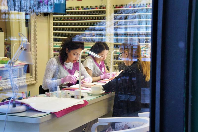 12.18.2018 Russia. Moscow.  Nail master makes a manicure client. view through the glass. royalty free stock photos
