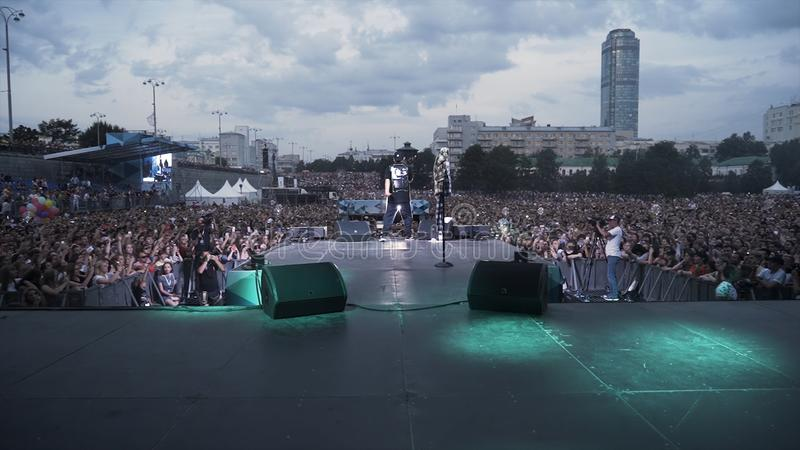 Russia - Moscow, 09.12.2019: Rap or Hip-Hop musician performing on stage in front of cheering crowd. Action. Rear view stock photo