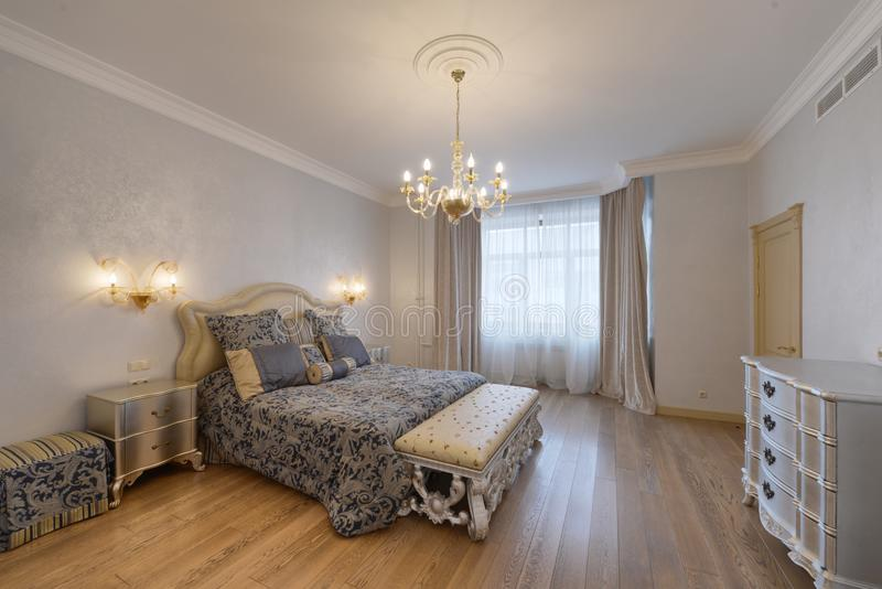 Russia, Moscow region - bedroom interior in a new luxury house.n. Russia, Moscow - modern designer renovation in a luxury building. Stylish bedroom interior with stock photography