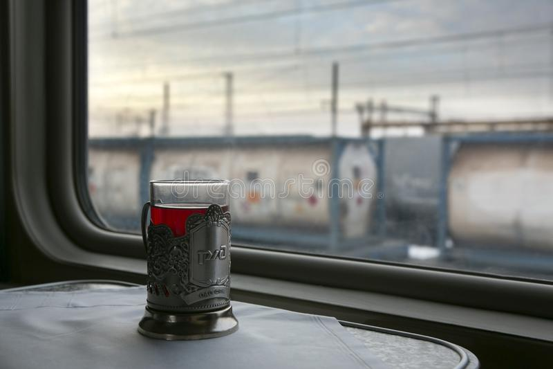 A glass of tea on the table in the train compartment. Outside the window trains royalty free stock photography