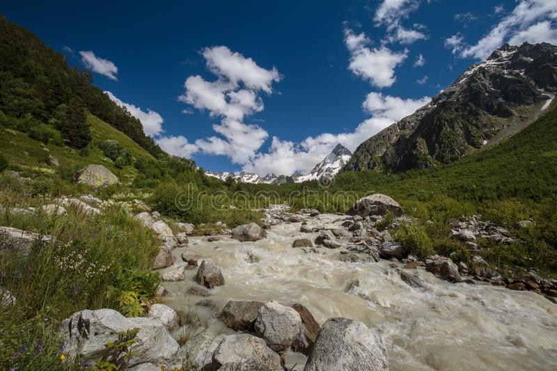 Movement of clouds and water flows in a stormy river in the Caucasus mountains in summer. Russia. Movement of clouds and water flows in a stormy river in the stock images