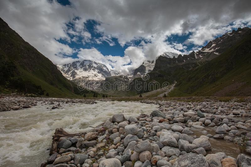 Movement of clouds and water flows in a stormy river in the Caucasus mountains in summer. Russia. Movement of clouds and water flows in a stormy river in the royalty free stock photography
