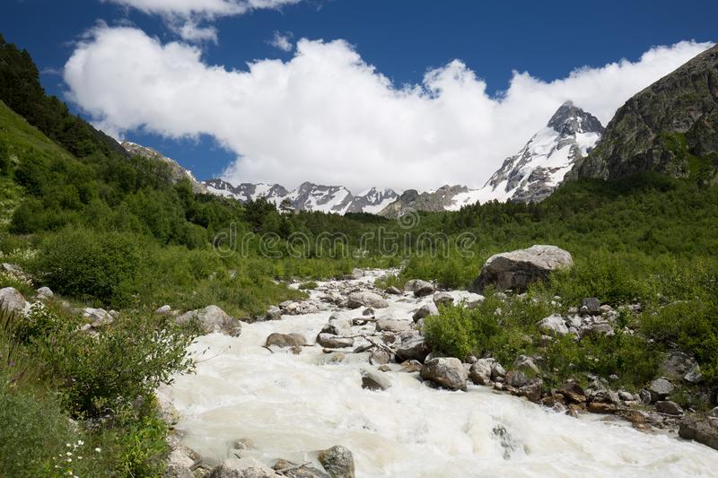 Movement of clouds and water flows in a stormy river in the Caucasus mountains in summer. Russia. Movement of clouds and water flows in a stormy river in the stock photo