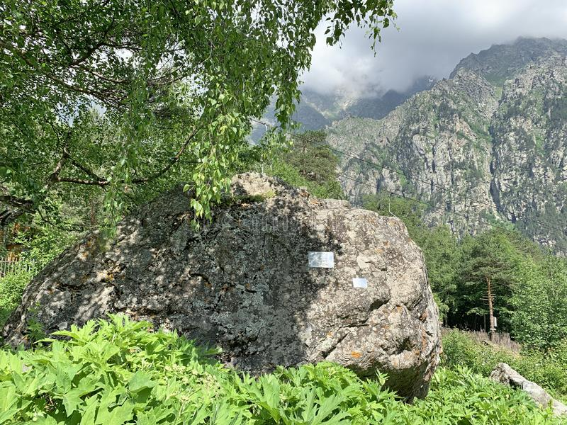 Russia, North Ossetia. Tsey gorge, memorial stone near the road to the  glacier `fairy Tale` in summer.  stock image