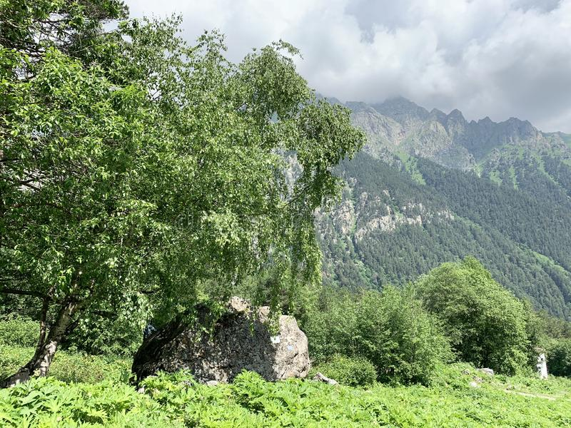 Russia, North Ossetia. Tsey gorge, memorial stone near the road to the  glacier `fairy Tale` in summer.  stock photography