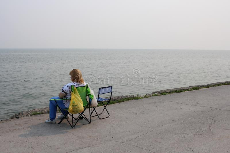 Russia, Novosibirsk, July 21, 2019: a woman sitting on the seafront resting in the morning on the reservoir stock photo